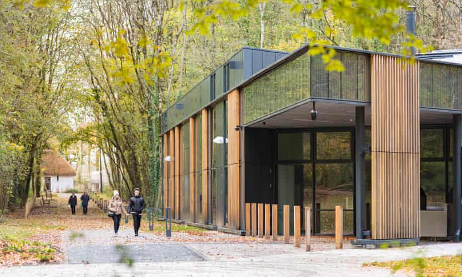 Couple walk hand in hand past the wood and glass design of the St Fagans National Museum of History in Cardiff, Wales.