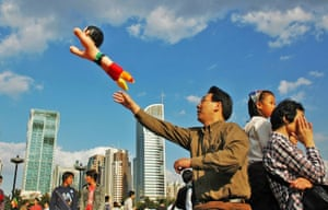 "Childlike Innocence by Shenghua Fan (finalist, single) ""People's Square, Shanghai, is a place for holiday-makers and visitors to enjoy the city's leisure activities: walking, chatting, playing games as a family. Here, a man plays with a child's plastic toy."""