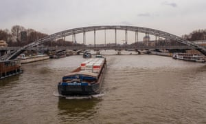 A container barge transporting Franprix grocery goods travels along the river Seine to the centre of Paris.