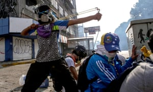 A protester takes aim at riot police with a sling shot during anti-government protests in Caracas, May 2017.