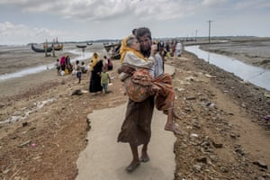 A Rohingya Muslim man Abdul Kareem walks towards a refugee camp carrying his mother Alima Khatoon after crossing over from Myanmar into Bangladesh, at Teknaf, Bangladesh