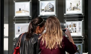 People look at property listings in an estate agents window