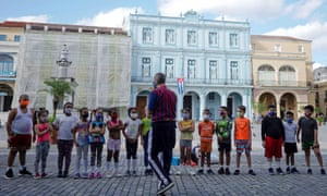 A teacher at a Cuban school explains the dangers of Covid to his students.
