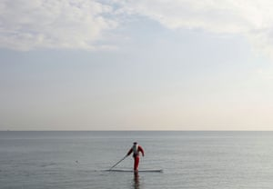 A man dressed as Santa Claus paddles on a board in Larnaca, Cyprus