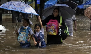 Girls and their mother wade through a flooded street in Mumbai