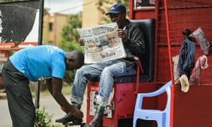 A man in Nairobi reads a newspaper carrying a headline about Pope Francis's visit to Africa.
