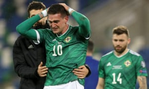 A dejected Kyle Lafferty is consoled by a team mate after Northern Ireland's defeat. .