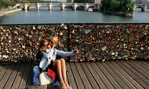 Lovers take a selfie on the lock-covered Pont des Art in Paris.