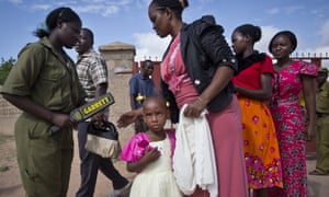 Christians are scanned with a metal detector outside the Our Lady of Consolation church, which was attacked with grenades by militants , in Garissa, Kenya