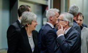Theresa May smiles as Jean-Claude Juncker points to a plaster on his face.