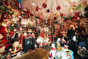 County Durham, UK. Victoria Burnham admires the hundreds of Santa Claus's as she finishes decorating her father's house in the village of Framwellgate Moor