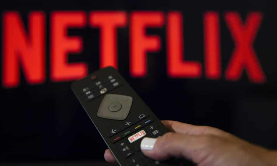 A person holds a remote control in front of the Netflix logo