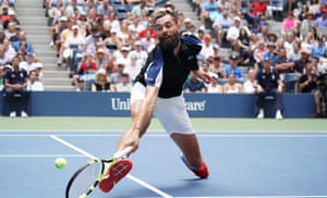 Benoit Paire stretches to return against Roger Federer.
