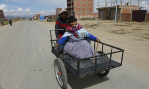 A woman is transported on a tricycle to a polling station to vote in El Alto.