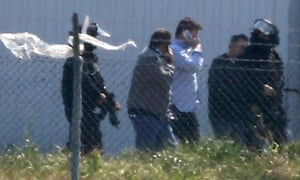 Passengers including Ben Innes are escorted away from the plane by police.