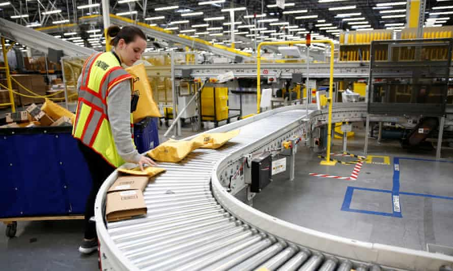 Alyssa Wells, an area manager, loads packages on to a conveyor line for scanning and labeling at the Amazon fulfillment center in Kent, Washington.