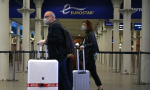 Passngers wearing a facemask arrive at the Eurostar terminal at St Pancras station in London on May 6, 2020.