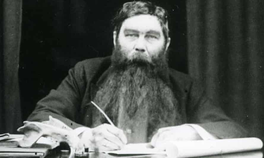 Conan Doyle in a very large false beard, writing at a desk with an animal skull on it