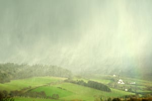 Illuminated by afternoon sunshine, showers of snow and hail sweep across a valley near Aberystwyth, Wales.