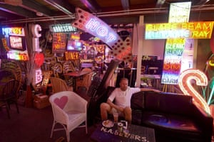 London, UK: A man relaxes amid an array of neon lights and signs inside the God's Own Junkyard gallery, cafe and workshop in east London