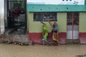 Dacope, Bangladesh. Residents head to shelter along a flooded street ahead of the expected landfall of Cyclone Amphan