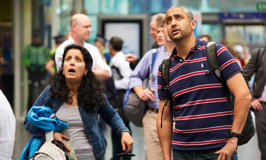 Rail passengers at Manchester Piccadilly station looking shocked as they look at the timetable.