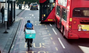 Deliveroo rider flanked by London double-decker