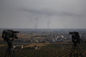 Television cameras are seen on a hilltop in Ceylanpinar, Turkey, as smoke billows from fires in Ras al-Ayn, Syria.