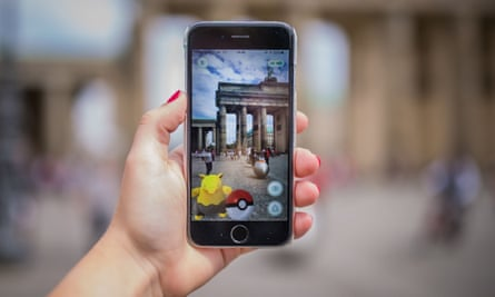 A woman points her smartphone at the Brandenburg Gate as she plays the Pokémon Go game in Berlin