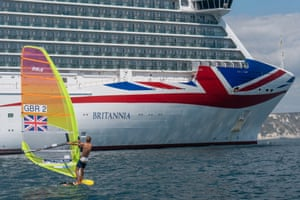 Tom Squires windsurfing past the MV Britannia P&O cruise ship at Weymouth Bay in Portland, Dorset during July 2020. At the time, seven large cruise ships were docked at Weymouth Bay due to the Covid-19 pandemic.