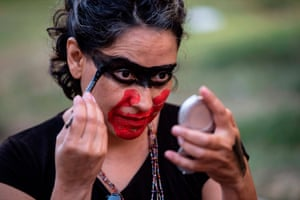 A woman applies face paint to look like a hand over her mouth before a rally