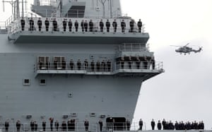 Sailors stand on board HMS Queen Elizabeth as it arrives in Portsmouth.