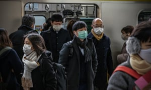 Commuters wearing face masks disembark from a train on Tuesday in Tokyo, Japan.