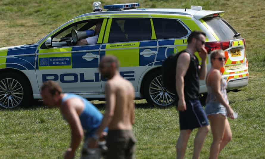 Police officers in a patrol car move sunbathers on in Greenwich park