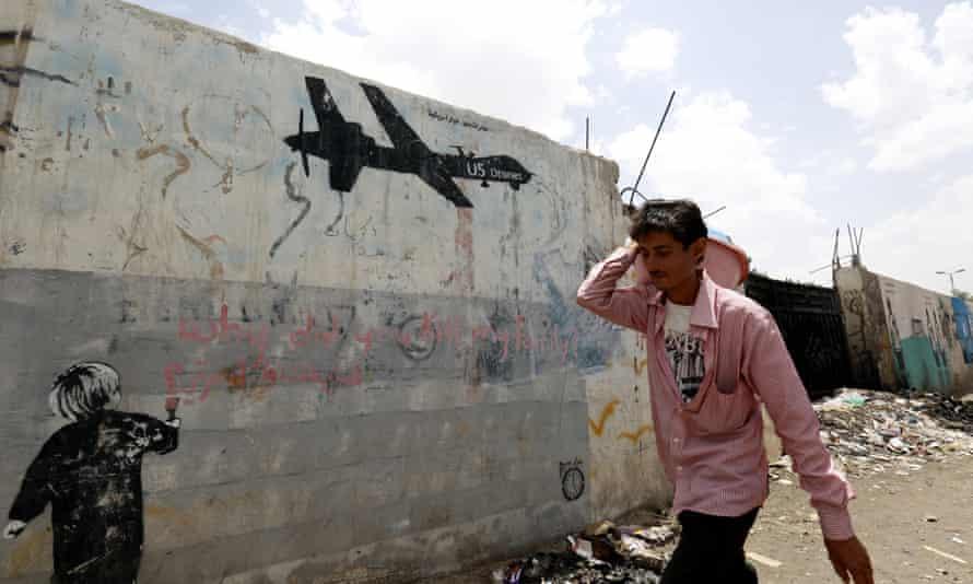 A man walks past graffiti in Yemen protesting against US drone strikes