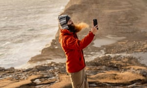 Side view of man standing on cliff edge taking a picture with mobile phone and admiring seascape.