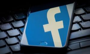 Facebook logo on iPhone resting on keyboard