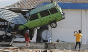 A man takes a photo of a car lifted into the air with his mobile phone following a massive earthquake and tsunami at Talise beach in Palu, Central Sulawesi, Indonesia