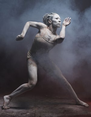 A woman covered in ochre in a contorted position