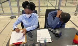 South African health ministry officials collect tracing forms from international travellers at Johannesburg's OR Tambo airport Monday 21 December 2020.