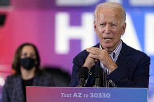 Joe Biden speaks as Kamala Harris listens in Phoenix, Arizona, on 8 October.