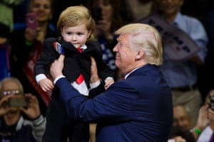Donald Trump holds as child dressed as him.
