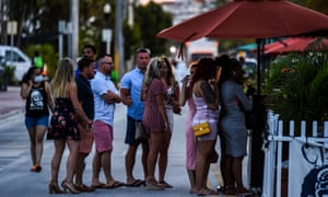 People wait to enter a restaurant in Miami Beach, Florida, on 26 June.