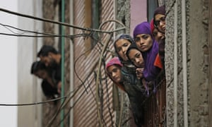 Indian Muslim women look out of a window as security officers patrol a street in Delhi