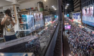 A man takes photographs in a shop above the chaotic pedestrian zone of Sai Yeung Choi Street South on the last day before vehicles returned.