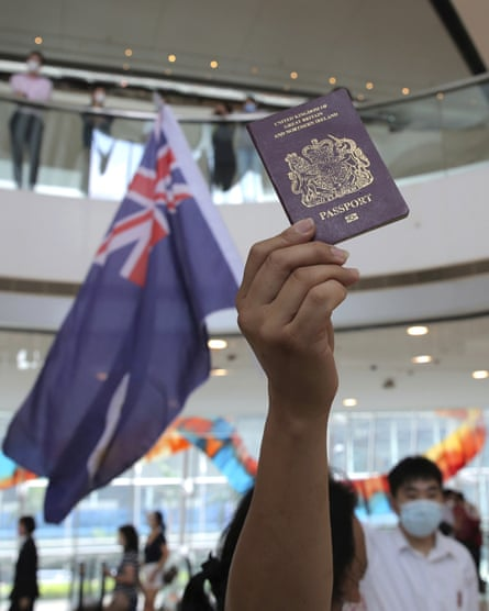 A demonstrator holds up a British national (overseas) passport in front of a Hong Kong colonial flag in shopping mall
