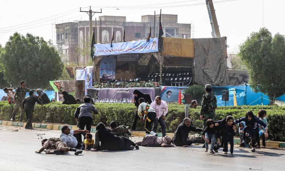 Iranian men, women, and children lying on ground and some seeking cover at the scene of the attack on a military parade.