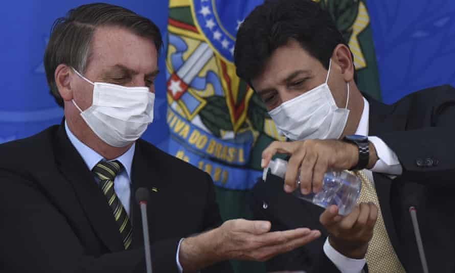 Luiz Henrique Mandetta offers President Jair Bolsonaro some anti-bacterial hand gel in Brasília on 18 March 2020.