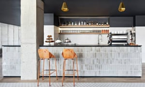 The cafe area at The Boro Hotel in Long Island City, New York. Two high wooden chairs sit next to a long counter featuring a coffee machine and cake stands.