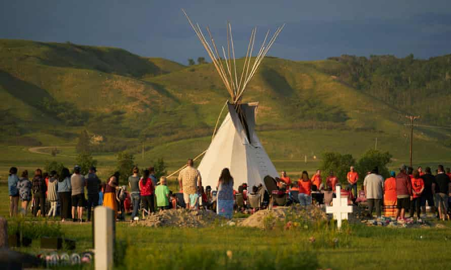 Hundreds of people gather for a vigil in a field where 751 human remains were discovered in unmarked graves by the Cowessess First Nation at the site of the former Marieval Indian residential school in Canada on 26 June. It was the second such shock discovery in less than a month.